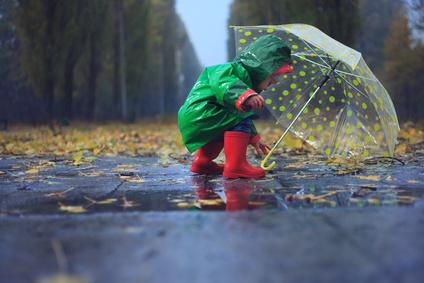 Kind mit Regenschirm und Gummistiefel im Herbst